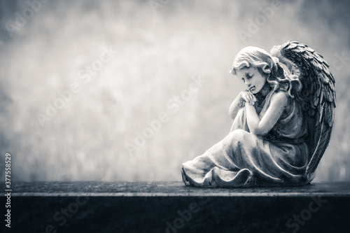 Photo Angel figure sitting on an old headstone in a cemetery