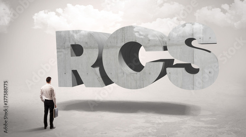 Photo Rear view of a businessman standing in front of RCS abbreviation, modern technol