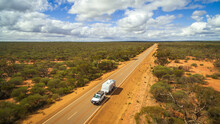 Aerial View Of 4WD And Modern Caravan On An Outback Highway In Australia Under A Blue Cloudy Sky