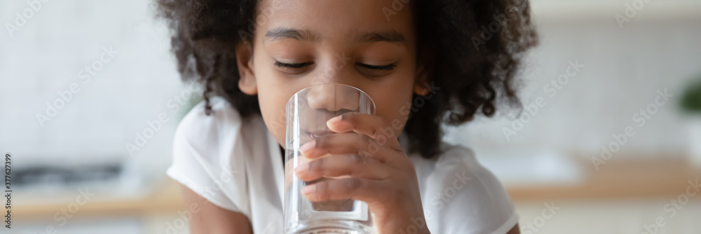 Fototapeta Thirsty funny small african ethnicity cute kid girl drinking fresh pure water, refreshing during day or enjoying morning healthcare routine, horizontal photo banner for website header design.