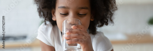 Thirsty funny small african ethnicity cute kid girl drinking fresh pure water, refreshing during day or enjoying morning healthcare routine, horizontal photo banner for website header design. - 377627399