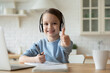 Leinwandbild Motiv Head shot adorable little european kid girl wearing wireless headphones, sitting in front of computer, enjoying online education courses at home, showing thumbs up gesture, e-learning concept.