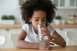 Leinwandbild Motiv Head shot thirsty small curly african american little child girl drinking glass water, hydrating organism indoors. Happy little mixed race kid enjoying morning healthcare routine alone in kitchen.