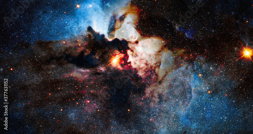 Obraz Nebula night starry sky in rainbow colors. Multicolor outer space. Star field and nebula in deep space many light years far from planet Earth. Elements of this image furnished by NASA. - fototapety do salonu