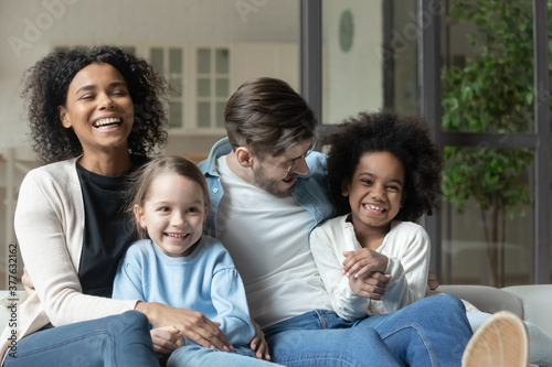 Stampa su Tela Happy emotional mixed race family relaxing together on comfortable couch indoors