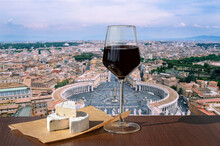 Glass Of Red Wine With Brie Cheese Against View Of Saint Peter's Square In Vatican, Rome, Italy. Rome Skyline. Panoramic View Of Old Rome. Cityscape Of Rome In Summer.