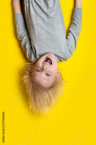 Fototapety, obrazy: Exciting blond boy hanging upside down on yellow background.