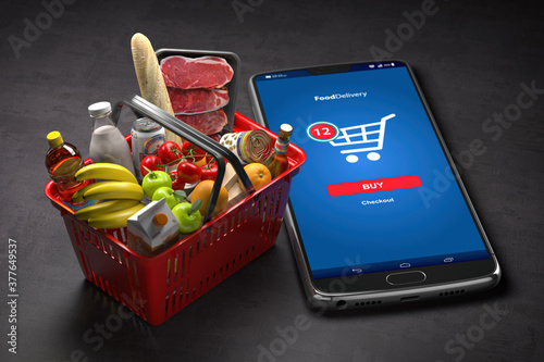 Fototapeta Shopping basket with fresh food and smartphone or mobile. Grocery supermarket, food and eats online buying and delivery concept. obraz