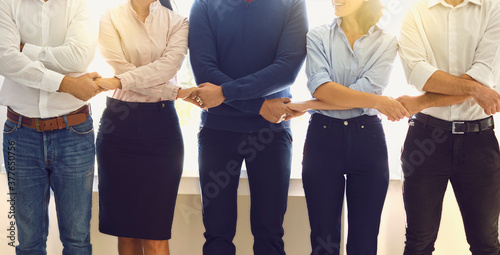 Photo Positive office employees standing in a row holding hands supporting each other