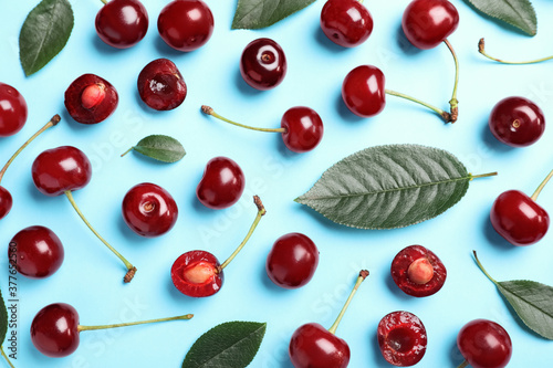 Fotografiet Sweet juicy cherries with leaves on light blue background, flat lay