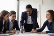 Leinwandbild Motiv Confident African American businessman hold lead meeting with diverse colleagues in office. Multiracial businesspeople brainstorm discuss company financial paperwork at briefing. Teamwork concept.