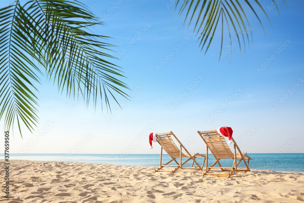 Fototapeta Sun loungers with Santa's hats on beach, space for text. Christmas vacation