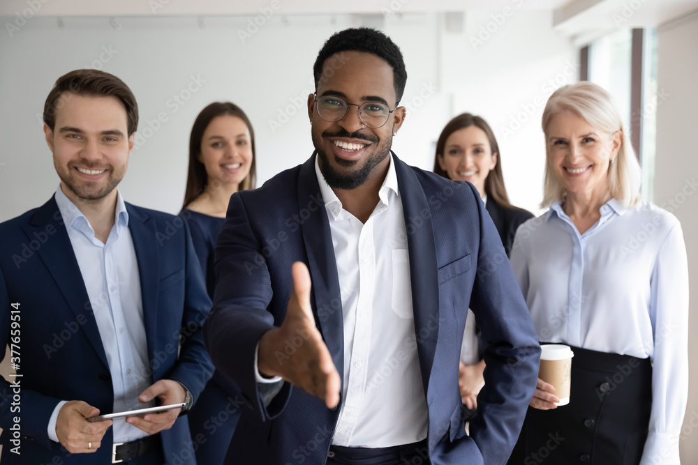 Fototapeta Portrait of smiling African American team leader stretch hand greeting job candidate or applicant in office. Happy multiracial businesspeople meet welcome newcomer at workplace. Employment concept.