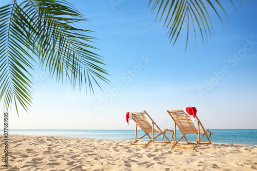 Fototapeta Sun loungers with Santa's hats on beach, space for text. Christmas vacation obraz