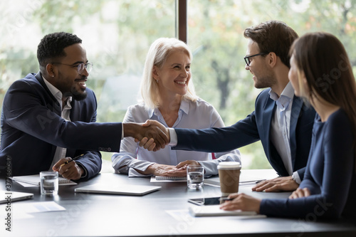 Smiling diverse businesspeople shake hands get acquainted greeting at team meeting in office. Happy multiracial male colleagues employees handshake at briefing with coworkers. Acquaintance concept.