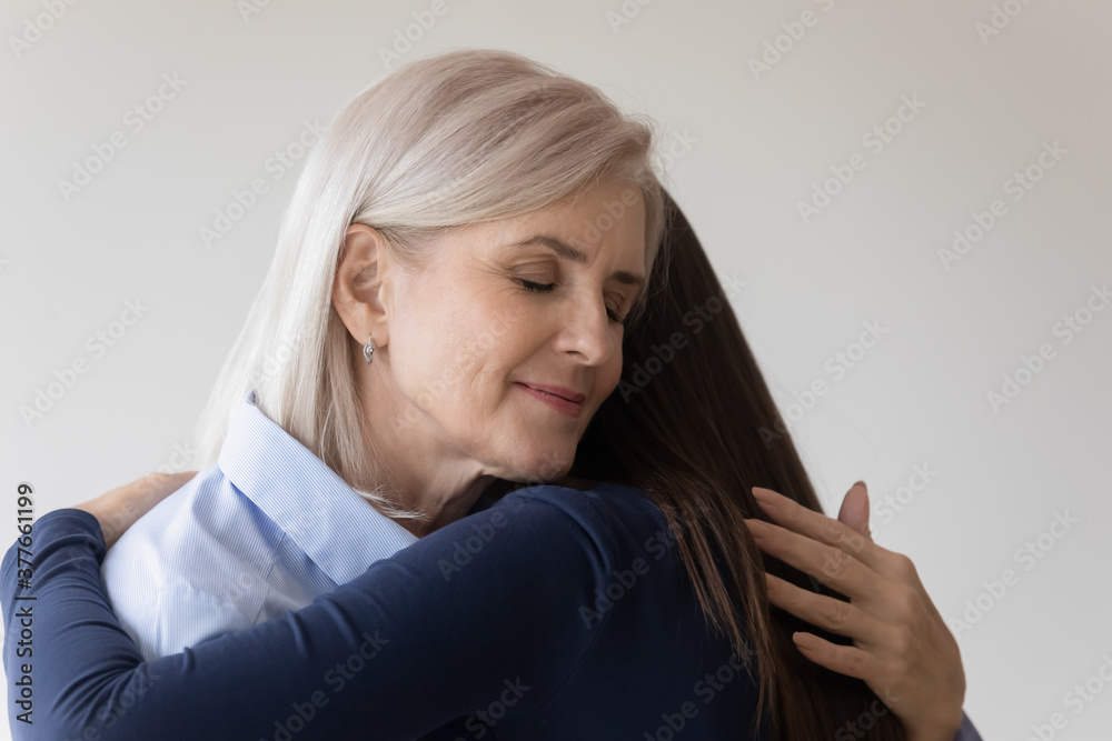 Fototapeta Happy Caucasian older 50s woman mother hug embrace grownup daughter reconcile make peace after fight. Smiling senior mom and adult girl embrace show love care in relationship. Family support concept.