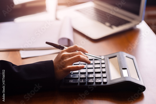 Fototapety, obrazy: Business women  working with calculator and  business document on office table in office. finance accounting concept.