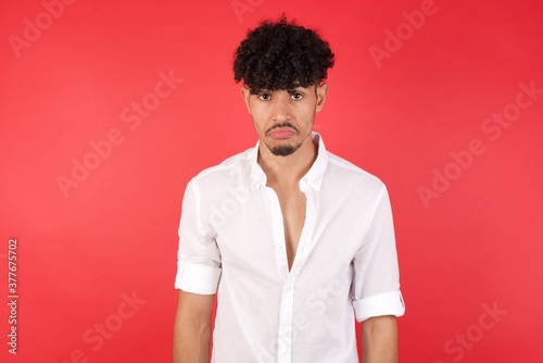 Portrait of displeased upset Young arab man with afro hair wearing shirt standin Wallpaper Mural