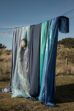 Teenage Girl Standing Behind Blue Drapes On Washing Line