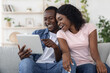 canvas print picture Cheerful black man and woman using digital tablet at home