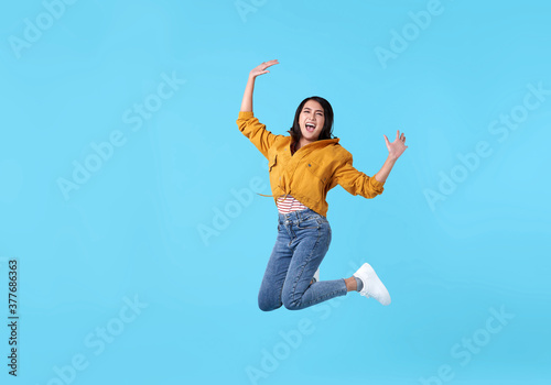 joyful young asian woman in yellow shirt jumping and celebrating over blue background Fototapet