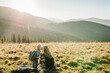 The daughter kiss parent on nature. Mom with backpack and child walk in the autumn grass. Family spending time together in mountain outside, on vacation. Holiday trip concept. World Tourism Day.