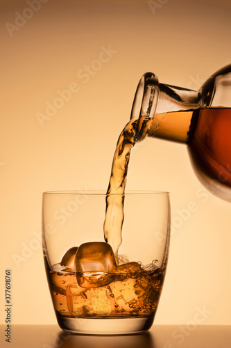 Fototapeta alcoholic drink, poured from a glass from a bottle on an orange gold background