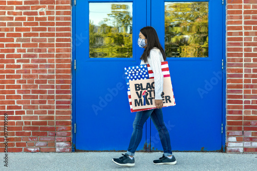 Fényképezés Female Taiwanese BLM Protestor Walking with Protest BLM and American Flag Signs