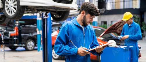 Caucasian mechanic in blue work wear uniform checks the vehicle maintenance checklist with blur lifted car in the background Fototapet