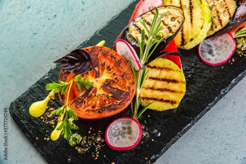 Tasty grilled vegetables on pan on dark background. Healthy food, summer food concept. © qwasder1987