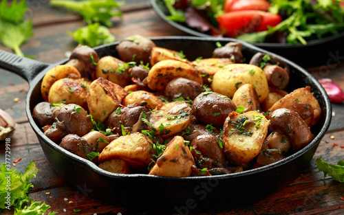Baked potato with mushrooms and herbs in iron cast pan on wooden table Fototapet