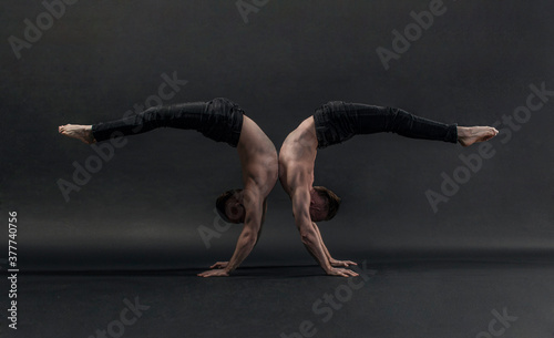 two twin brothers in black jeans with a naked torso perform acrobatic elements, black background