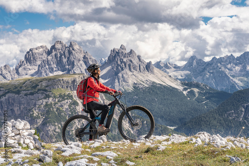 nice and active senior woman riding her electric mountain bike on the high plateau of Pratto Piazzo in the three peaks Dolomites , rocky silhouette of Mount Cristallo in background, South Tirol, Italy #377741953