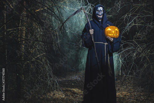 Fotografiet Woman devil ghost demon costume horror and scary she holding pumpkin in hand in the forest