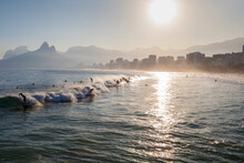 Surfers Surfing At Sunrise In Rio De Janeiro, Brazil. Urban Buildings Under The Sun Far Away And Nice Ocean View. Travel Destination Holiday Vacation New Normal Reopening Concept.