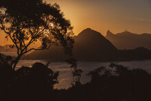 Beautiful View The Sea And A Chain Of Mountains Silhouette At Sunset Against Orange Sky; Mount Corcovado, Rio De Janeiro, Brazil. Trees And Vegetation Silhouette In The Foreground. Copy Space For Text