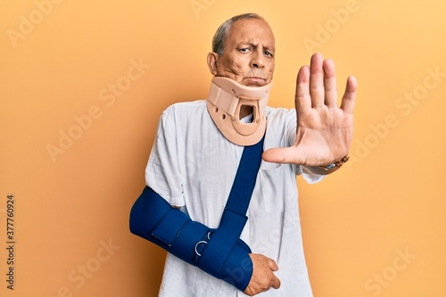 Handsome mature senior man wearing cervical collar and arm on sling doing stop sing with palm of the hand Fototapet