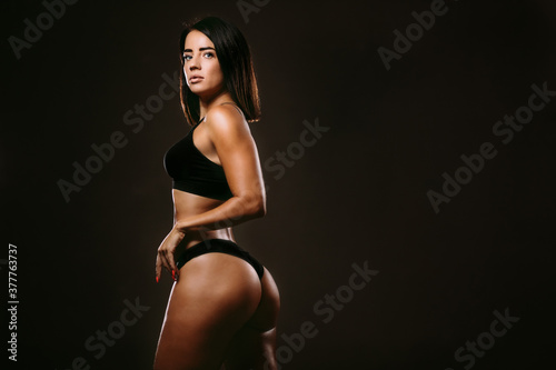 sexy fitness woman posing in underwear on black background Beautiful woman with sexy body wearing black fitness underwear and posing.