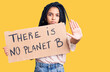 canvas print picture - Cute african american girl holding there is no planet b banner with open hand doing stop sign with serious and confident expression, defense gesture