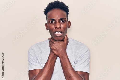 Photo Young african american man wearing casual clothes shouting and suffocate because painful strangle