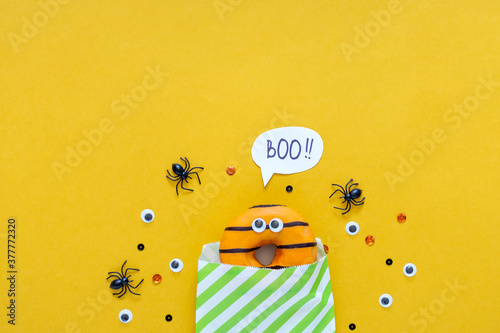 Fototapeta Happy halloween holiday concept. Funny food for kids - scared donuts in paper bag on bright yellow background with black spider and eyes. Halloween party greeting card. Spelling word Boo flat lay obraz