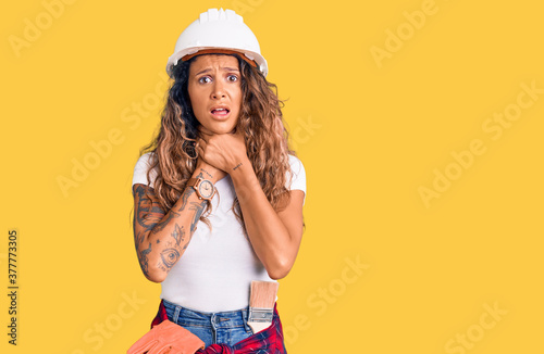 Young hispanic woman with tattoo wearing hardhat and builder clothes shouting and suffocate because painful strangle Canvas Print