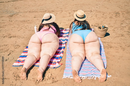 Obraz Backview of two plus size overweight sisters twins women relaxing lying on a towel at the beach on summer holidays - fototapety do salonu