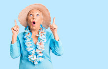 Senior Beautiful Woman With Blue Eyes And Grey Hair Wearing Summer Hat And Hawaiian Lei Amazed And Surprised Looking Up And Pointing With Fingers And Raised Arms.