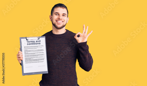 Obraz Young handsome man holding clipboard with terms and conditions document doing ok sign with fingers, smiling friendly gesturing excellent symbol - fototapety do salonu