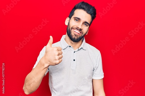 Valokuvatapetti Young handsome man with beard wearing casual polo doing happy thumbs up gesture with hand