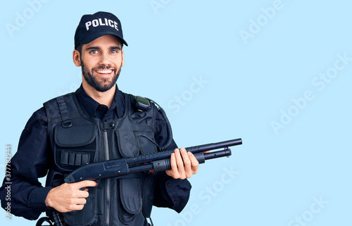 Obraz na plátně Young handsome man with beard wearing police uniform holding shotgun looking pos