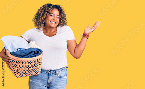 Fotografia Young african american plus size woman holding laundry basket celebrating victor