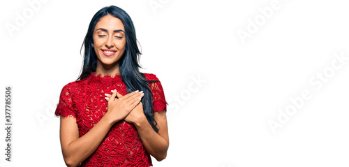 Beautiful hispanic woman wearing elegant shirt smiling with hands on chest with closed eyes and grateful gesture on face Canvas-taulu