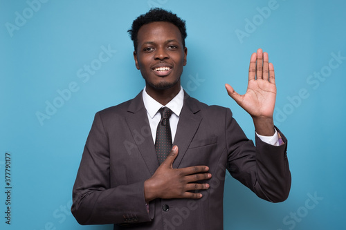 Photo African american man wearing suit smiling swearing with hand on chest and hand up, making a loyalty promise oath